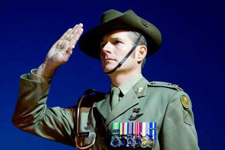 An Australian Army soldier salutes at an ANZAC Day dawn service.